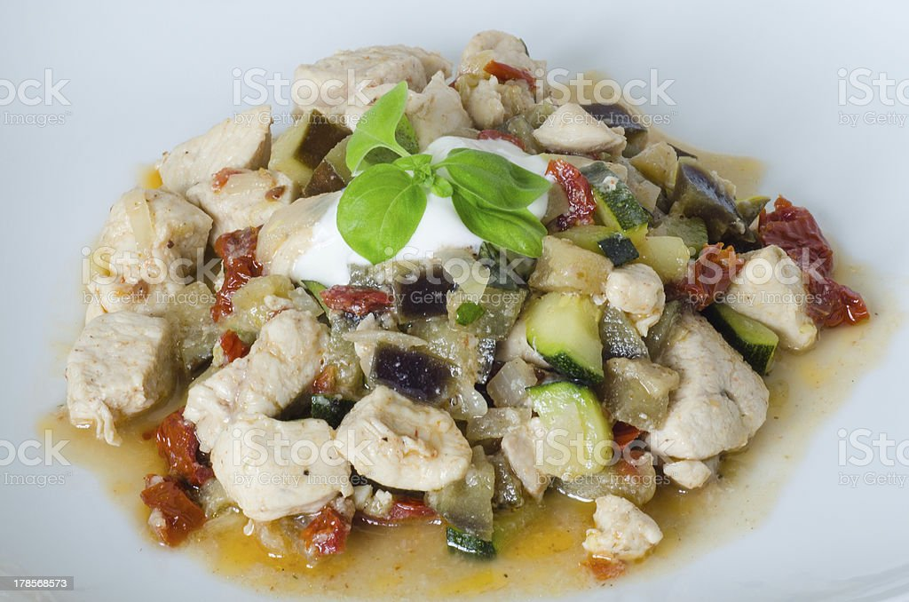 Garnished chicken with dried tomatoes, aubergine, zucchini and basil royalty-free stock photo
