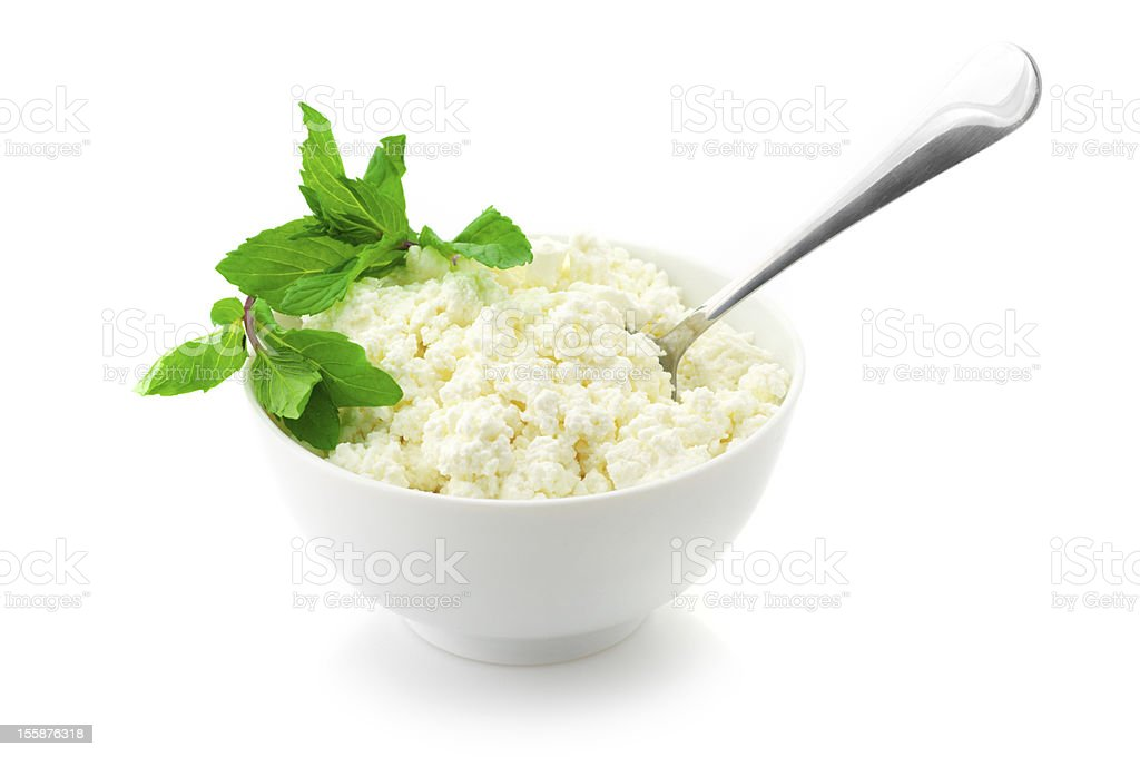 Garnished cottage cheese in a white bowl with a spoon stock photo