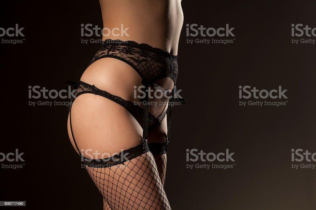 garter, sexy panties and fishnet stockings on dark background stock photo