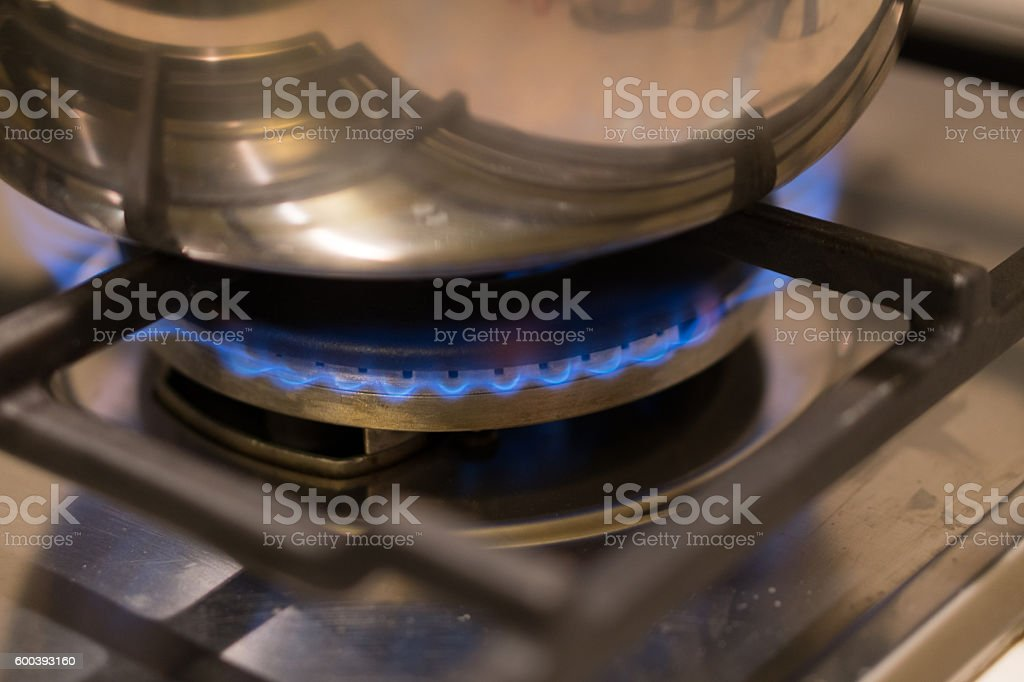 Gas burning under a stainless saucepan on a stove stock photo