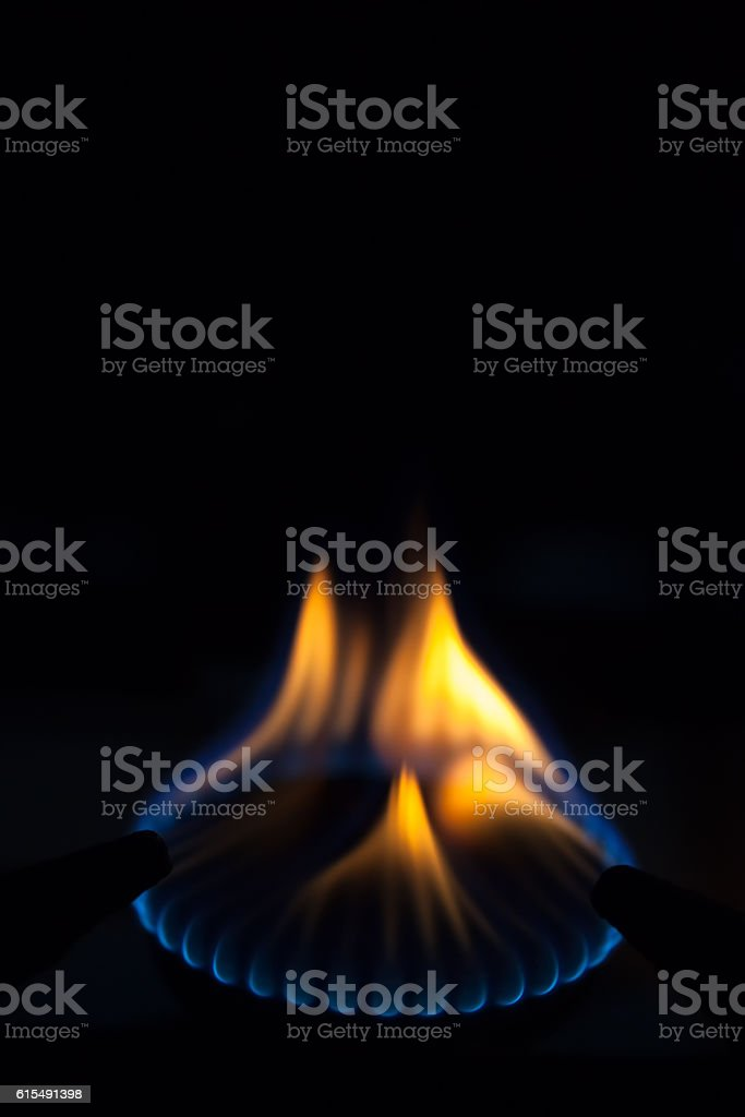 Gas burns on the burner on the stove in dark stock photo