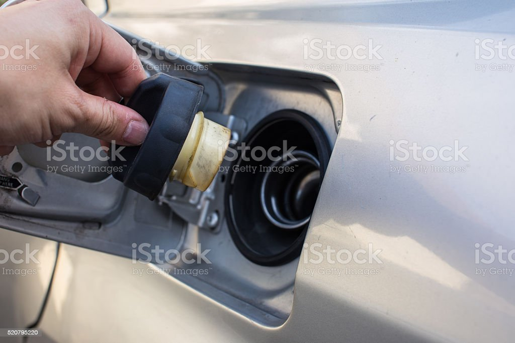 Gas cap with hand near fuel pump stock photo