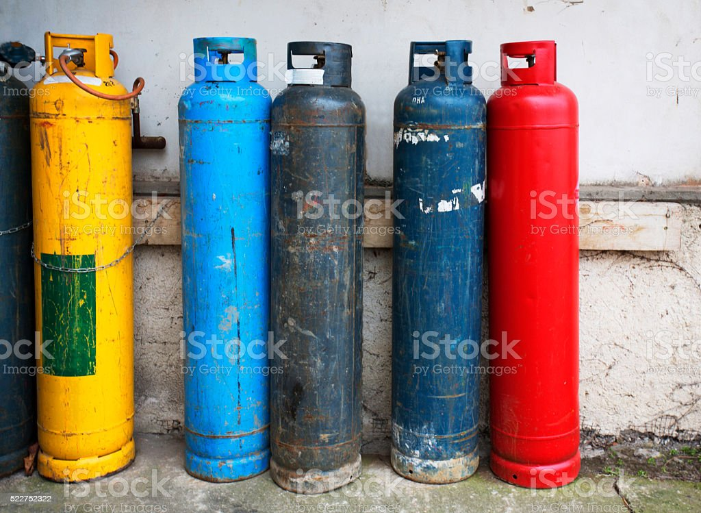 Gas cylinder. Industrial propane butane bombs. Row dirty gas cylinders. stock photo