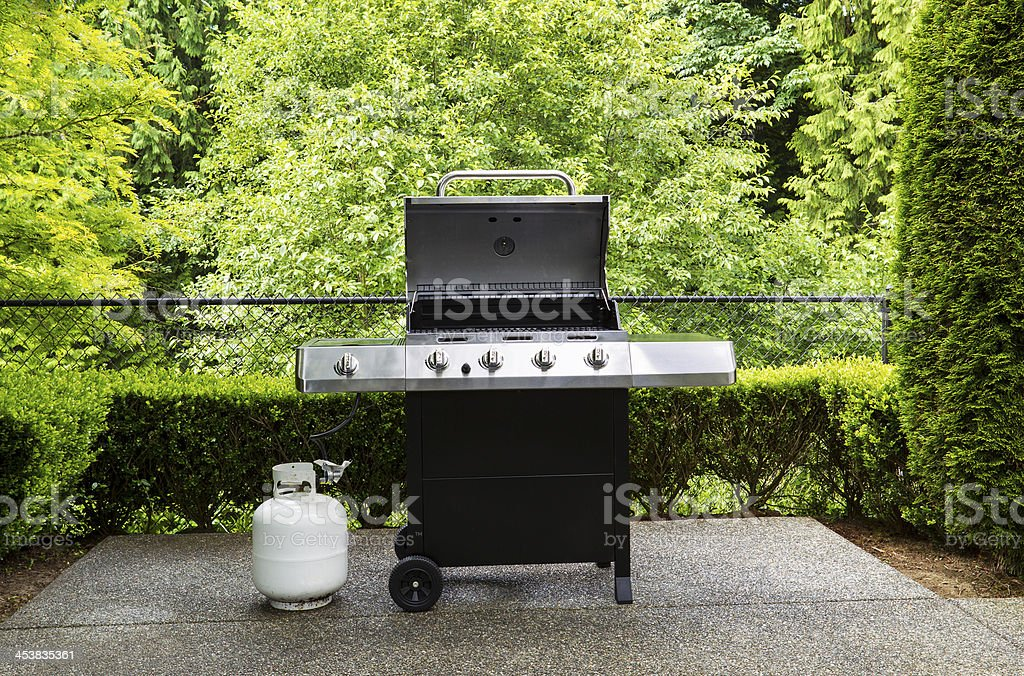 Gas grill with white tank on outdoor patio stock photo