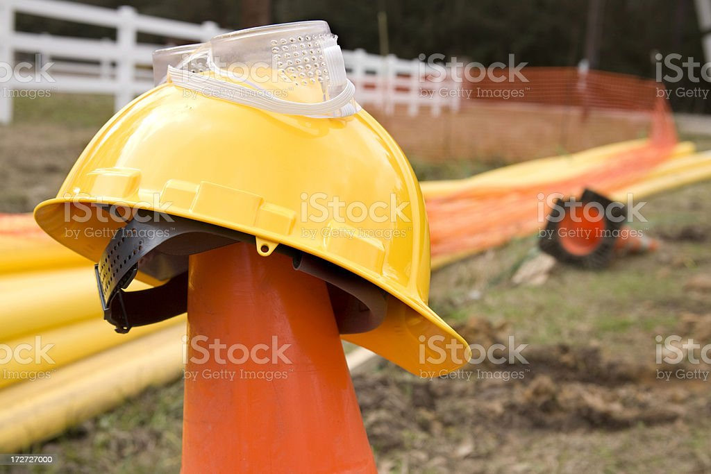 Gas line construction site. Orange pylon cone, hardhat. Pipelines. Rural. royalty-free stock photo