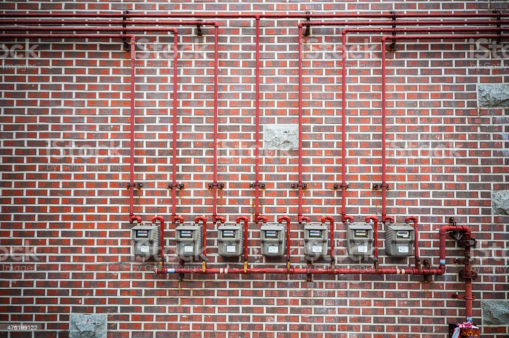 Gas meters and pipe on brick wall stock photo
