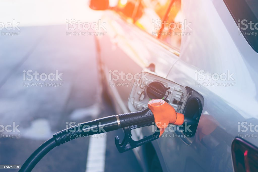 Gas nozzle pumping gas into a gray blonde car stock photo