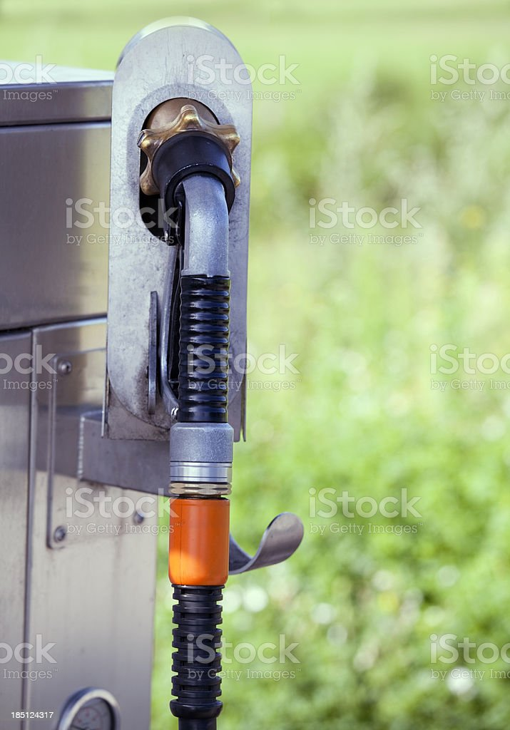 gas pump nozzle with green nature background stock photo
