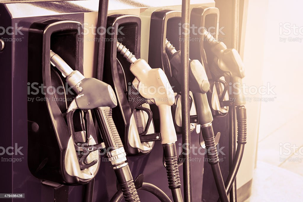 Gas pump nozzles in service station,vintage  filter stock photo