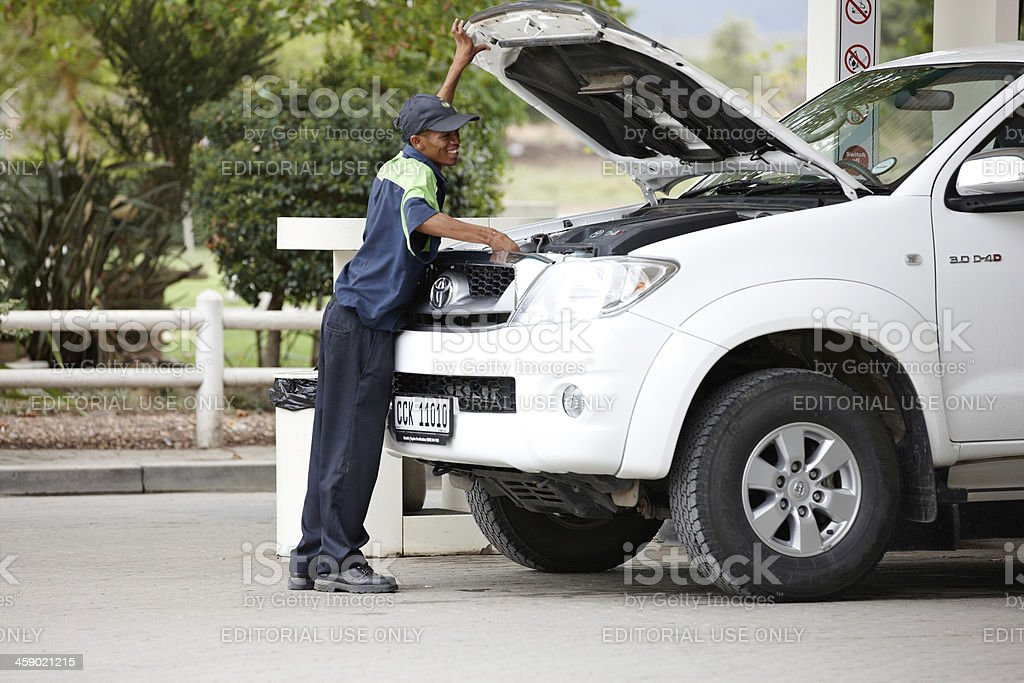 Gas station attendant checking oil royalty-free stock photo