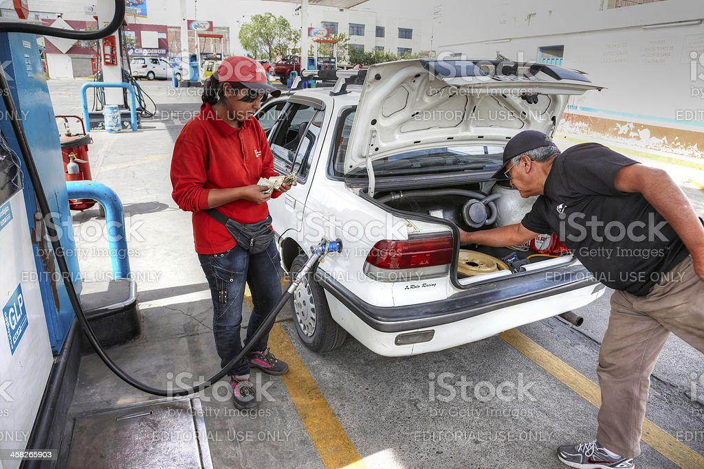 Gas station attendant filling hybrid car royalty-free stock photo