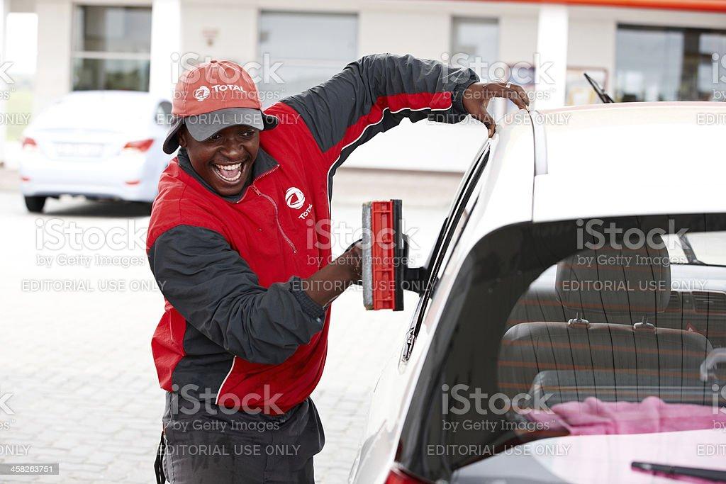 Gas station attendant washing windscreen royalty-free stock photo