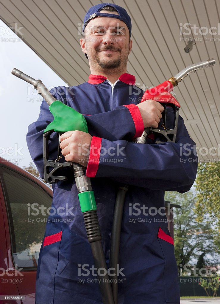 Gas station attendant with pumps royalty-free stock photo
