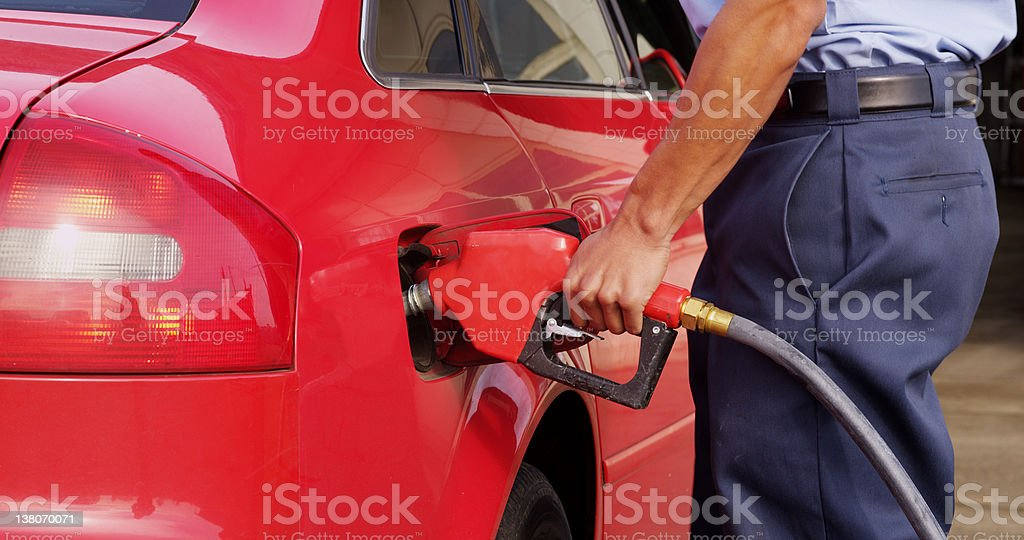 Gas station worker pumping fuel, closeup royalty-free stock photo