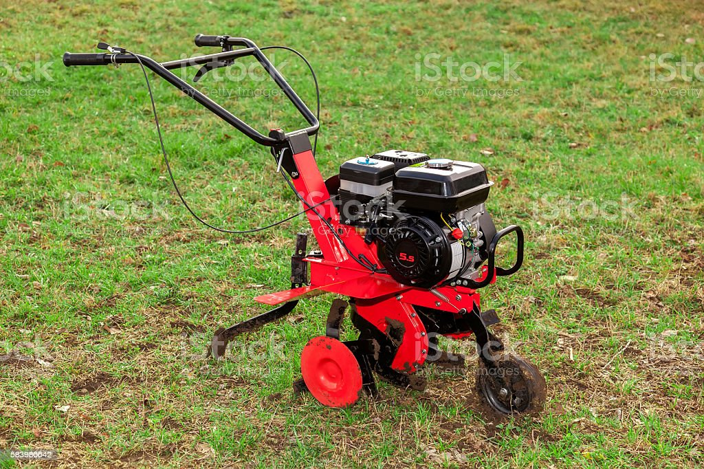 Gasoline cultivator for small agricultural works on green grass stock photo