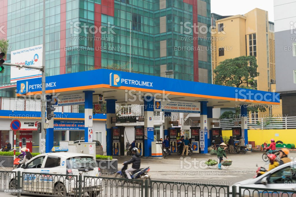 Hanoi, Vietnam - Mar 15, 2015: Gasoline station with vehicles running on busy street. A woman with conical hat carrying baskets of vegetable - the common image of Vietnam stock photo