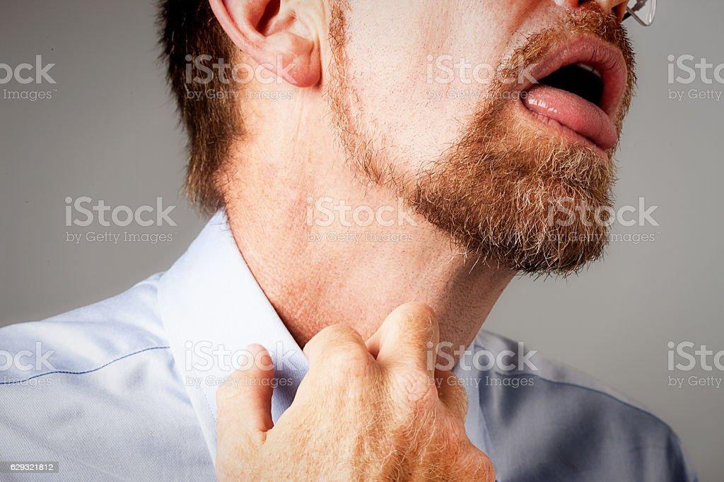 Gasping man loosens collar stock photo