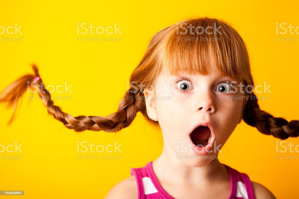 Gasping Red-Haired Girl with Upward Braids and Surprised Look royalty-free stock photo