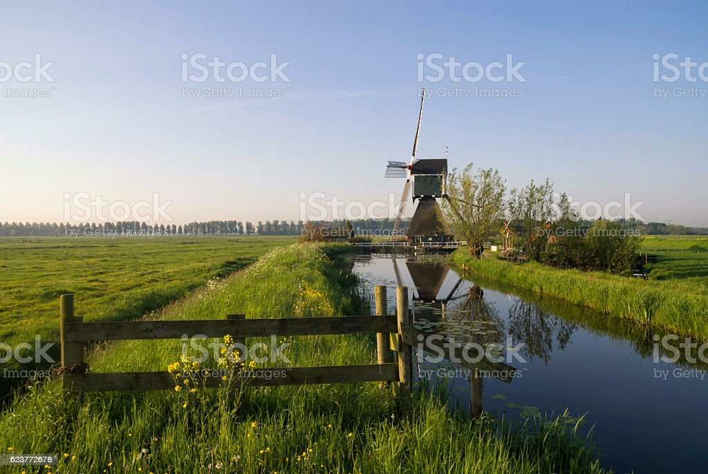 Gate in front of a windmill stock photo
