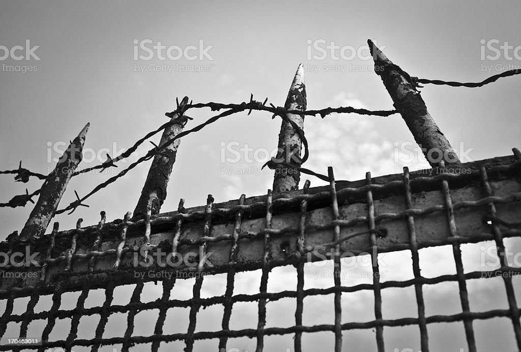 Gate With Iron Points And Barbed Wire, Black & White royalty-free stock photo