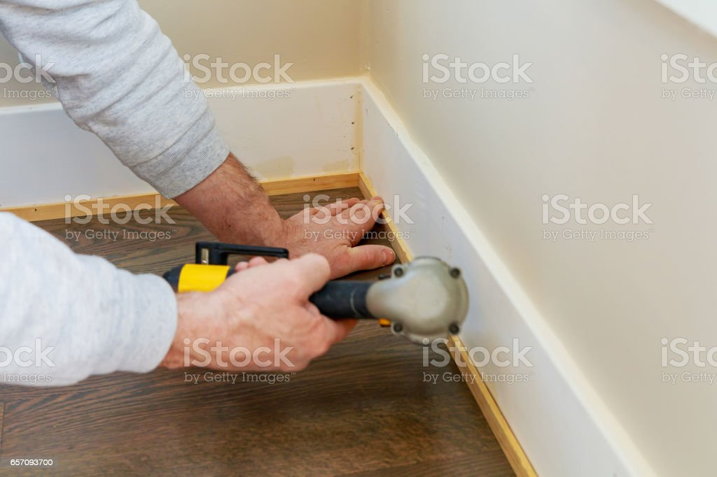 Gauge Finish Nailer man nailed slats custom house building contractor up a wall section for luxury stock photo