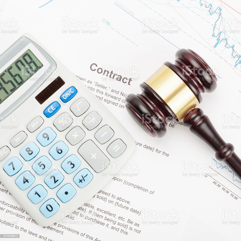 Gavel and calculator over contract - close up shot stock photo