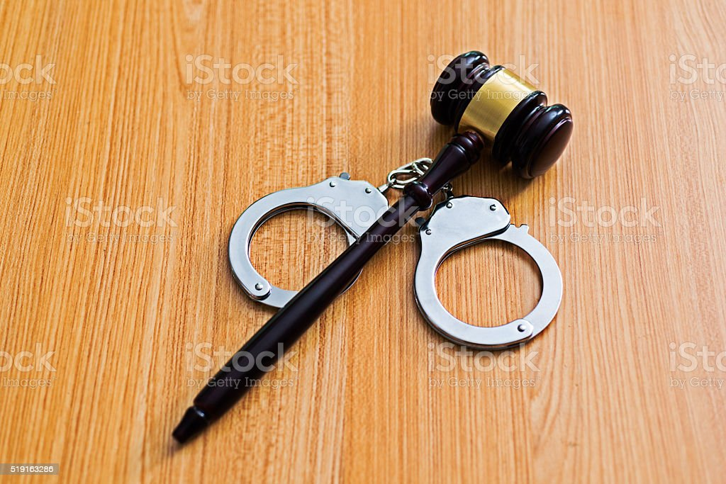 Gavel and handcuffs on desk stock photo