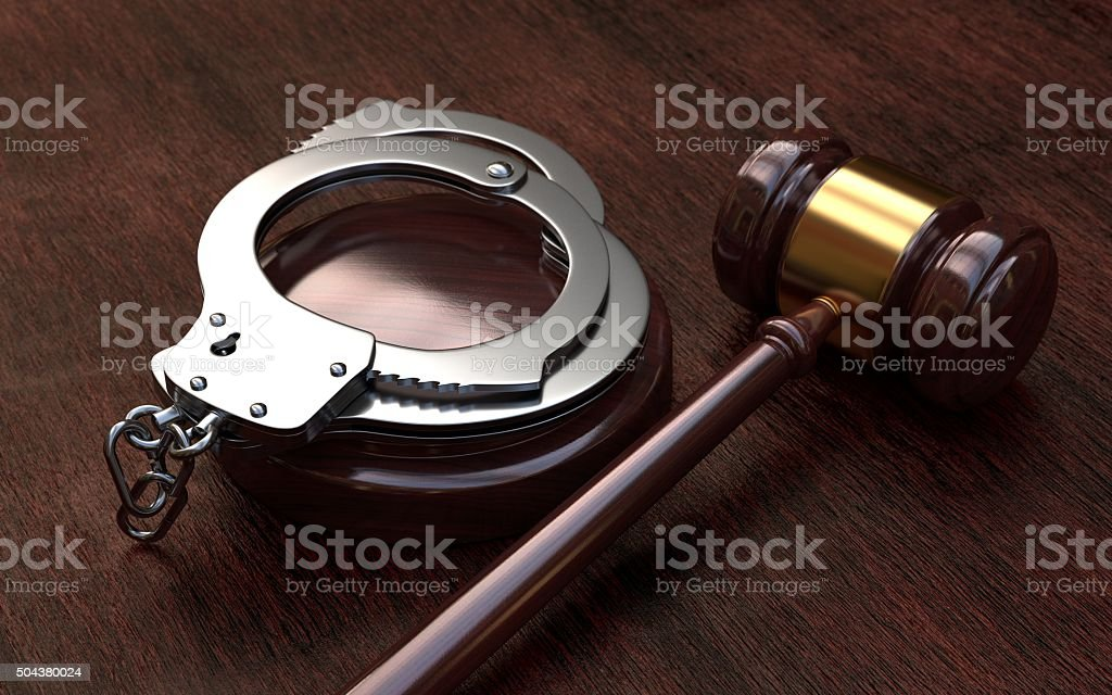 Gavel and handcuffs on wooden table background stock photo