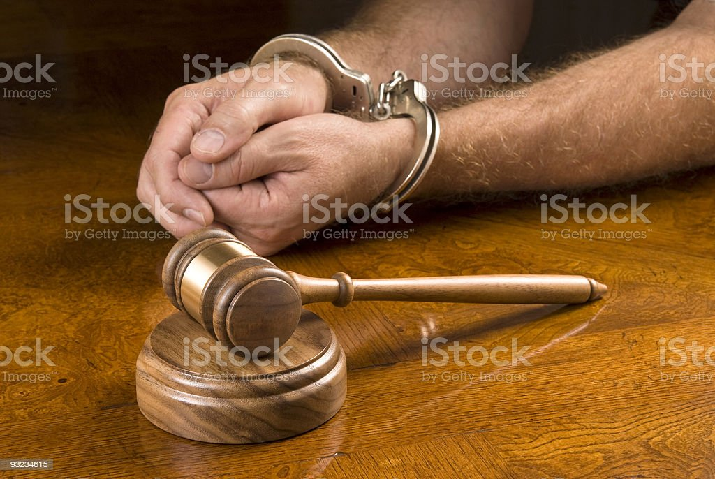 Gavel and man in handcuffs stock photo