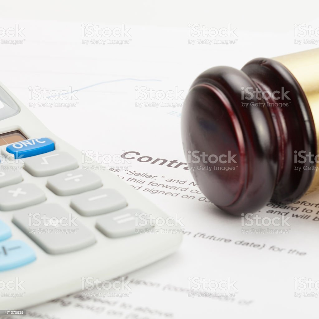 Gavel and neat calculator over contract - close up shot stock photo