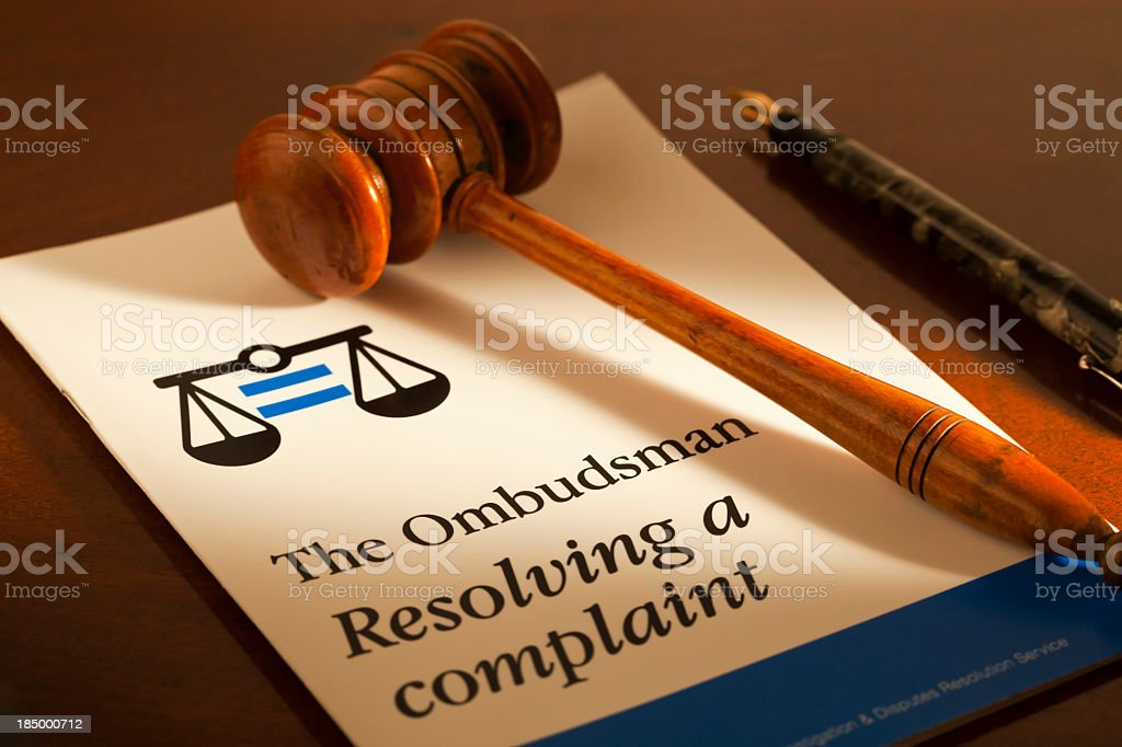 A gavel and pen displayed with an Ombudsman guidance leaflet royalty-free stock photo