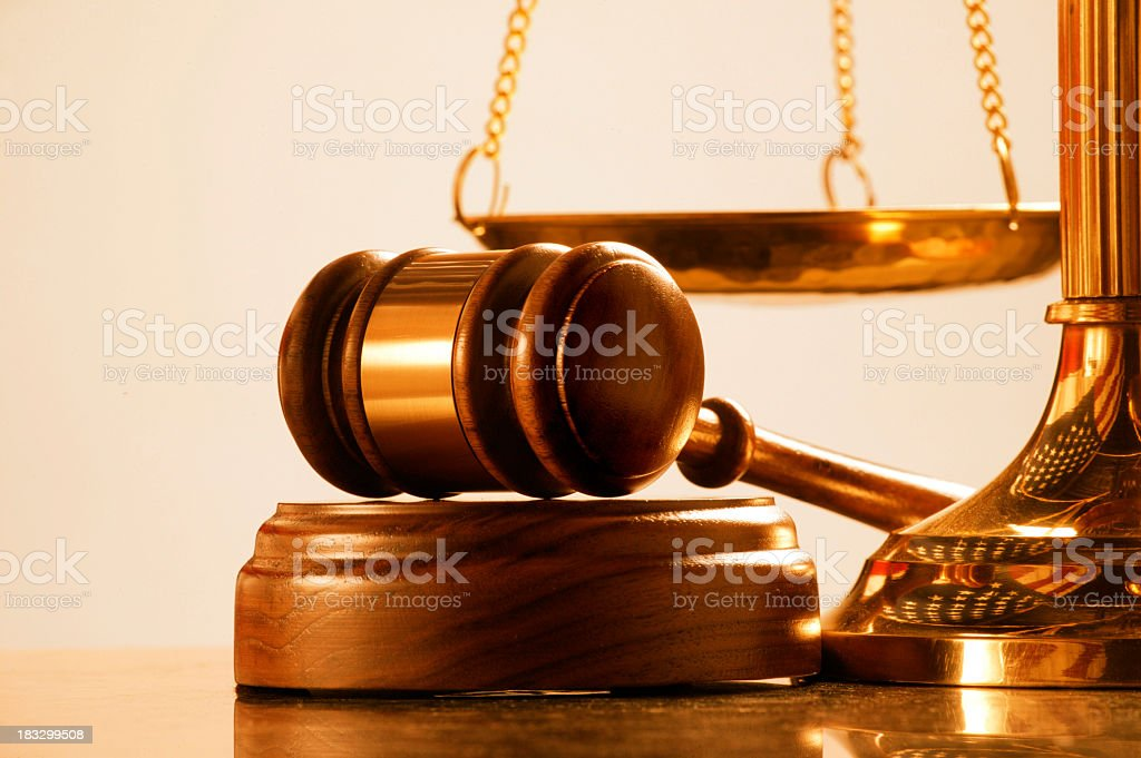 Gavel and sound block at base of brass scale of justice stock photo