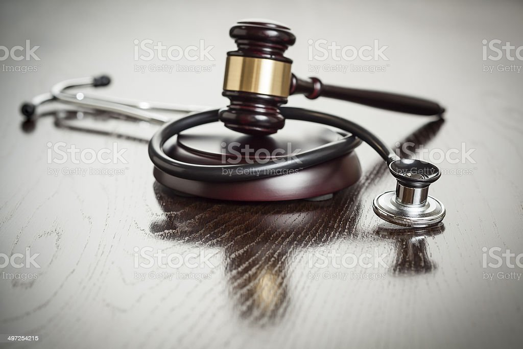 Gavel and Stethoscope on Reflective Table stock photo
