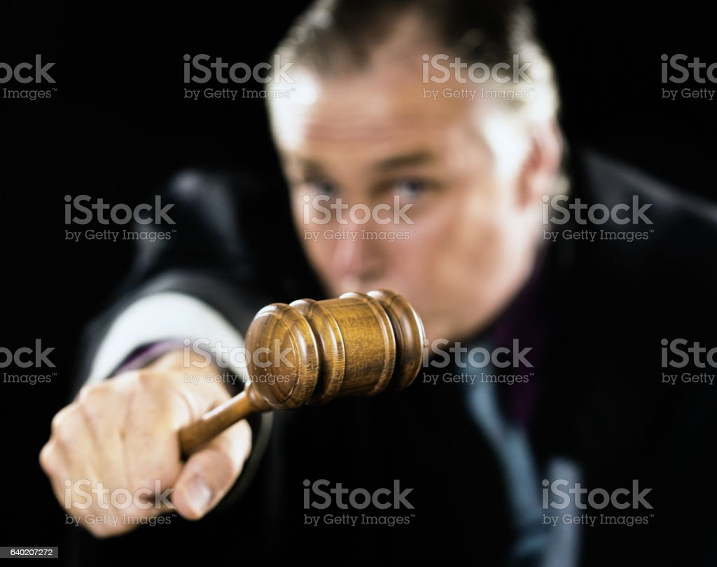 Gavel is held out as a threat by angry judge stock photo