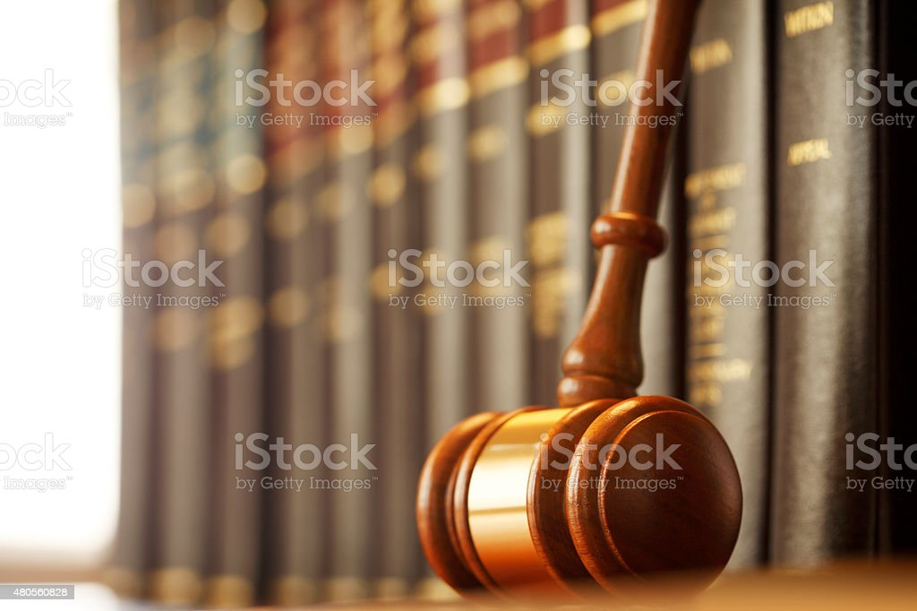 Gavel Leaning Against A Row Of Law Books stock photo