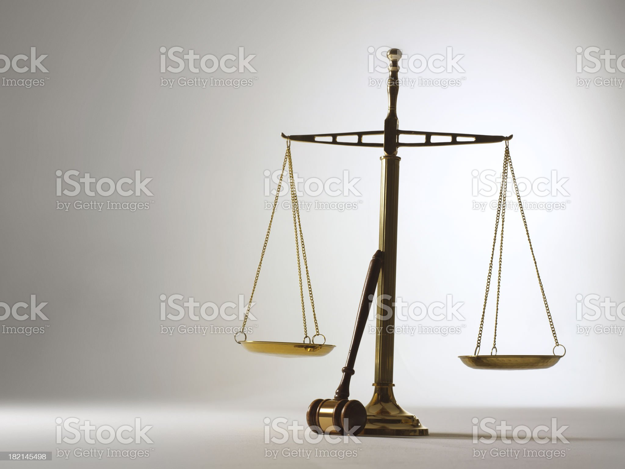 Gavel leaning against scales of justice on gray background royalty-free stock photo