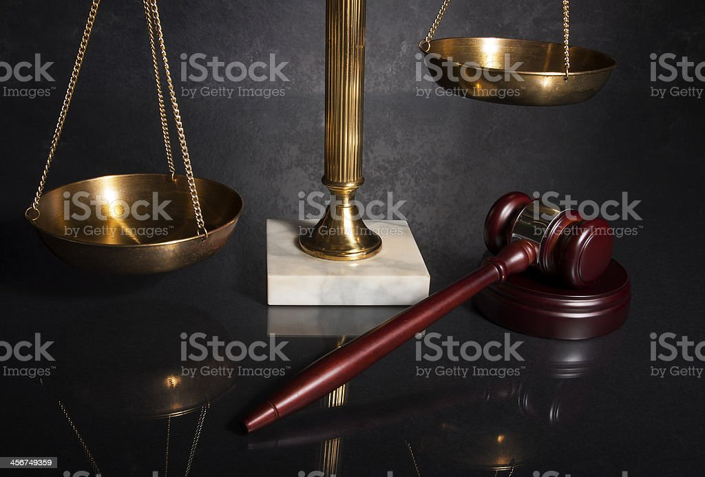 Gavel next to brass scales mounted on marble stock photo