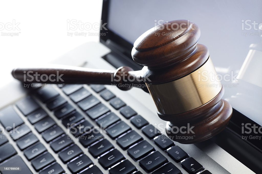 Gavel resting on a laptop computer stock photo