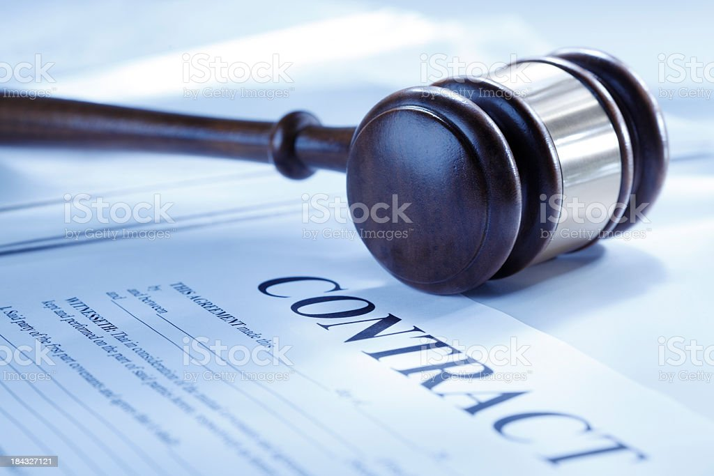 Gavel resting on an unsigned contract stock photo