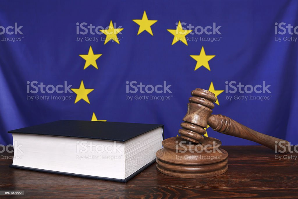 A gavel with a black book and a blue and yellow flag royalty-free stock photo