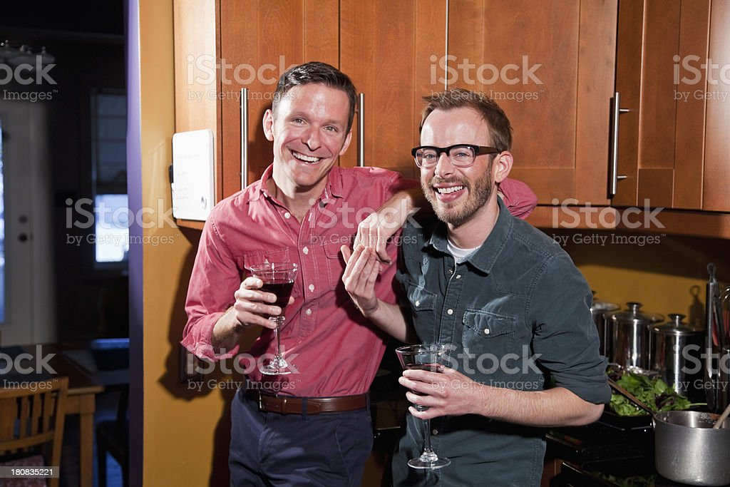 Gay couple in kitchen drinking wine royalty-free stock photo