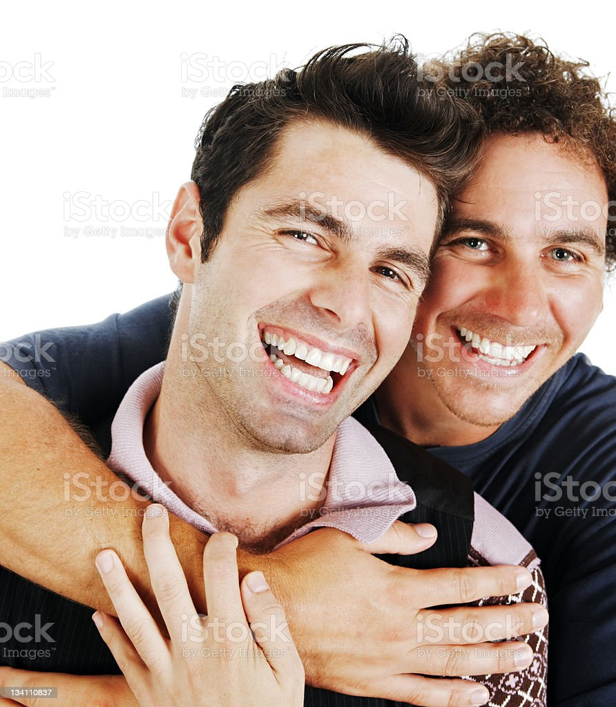 Gay couple laugh as they embrace stock photo