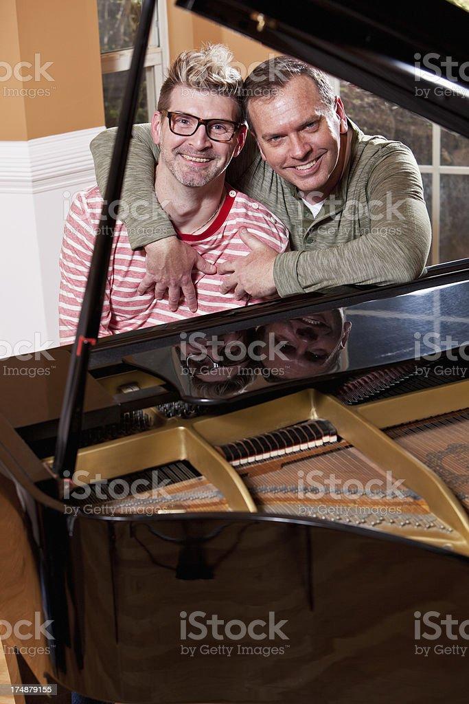 Gay couple playing piano royalty-free stock photo
