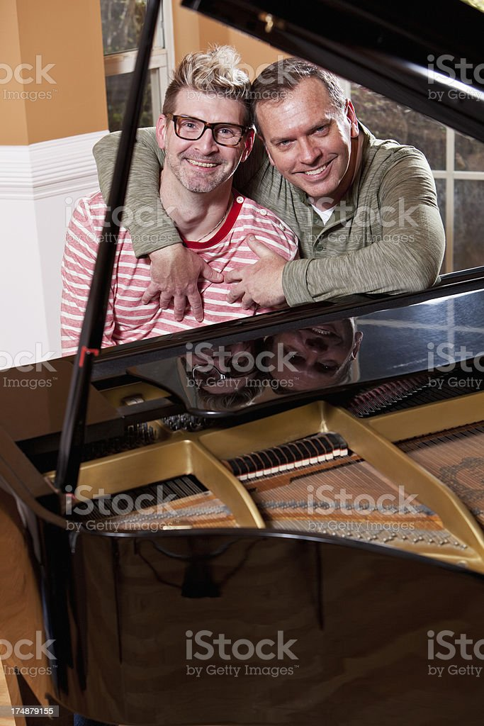 Gay couple playing piano stock photo