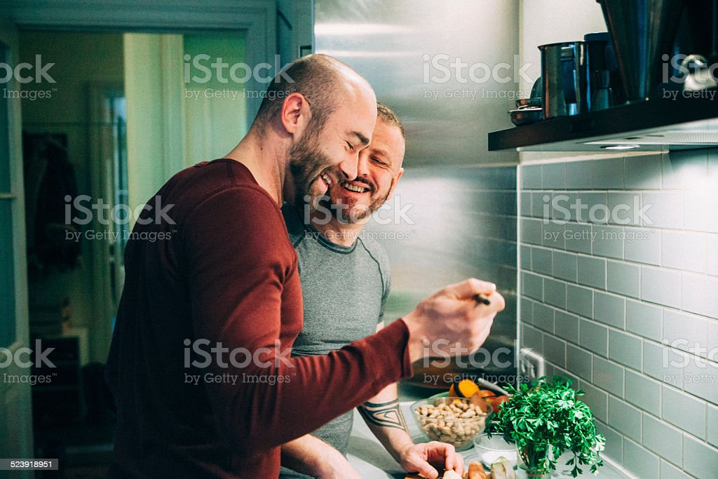 gay couple preparing the meal in the kitchen stock photo