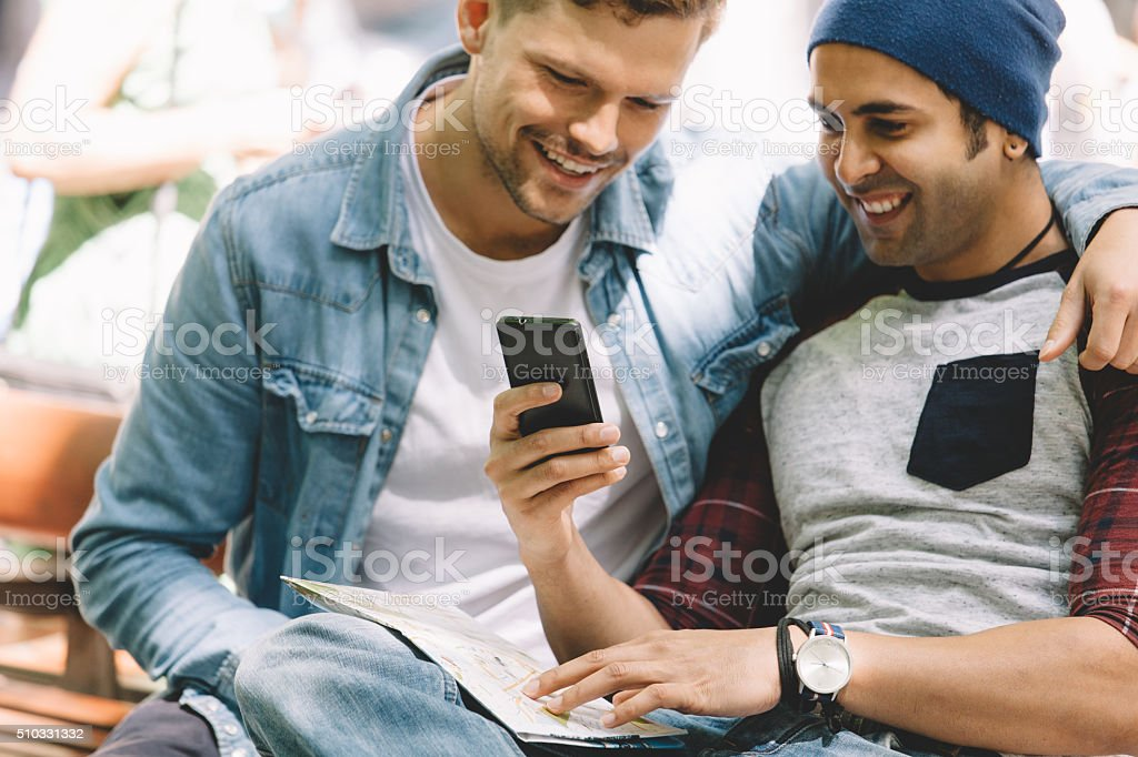 gay couple sharing something on the cellphone. stock photo