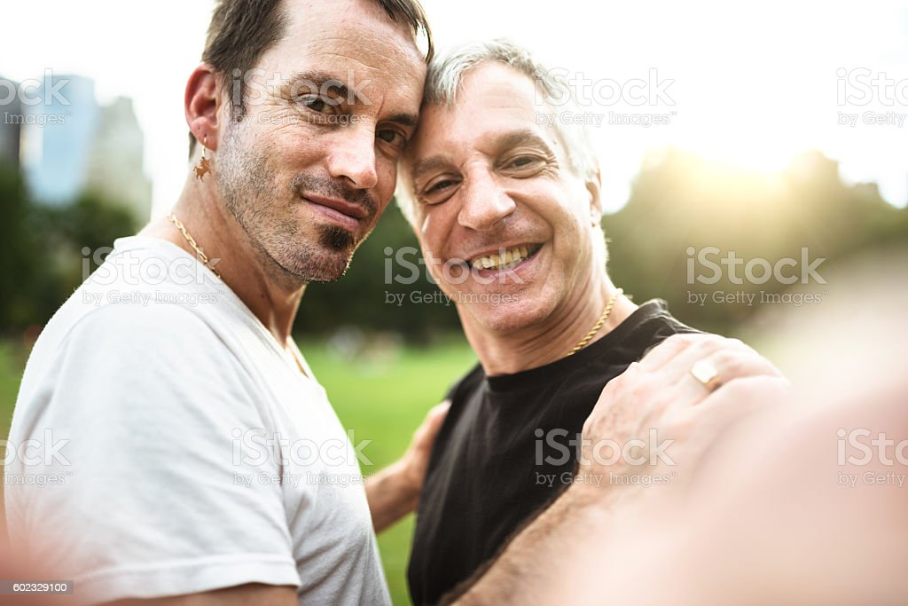 Gay couple take a selfie on the park stock photo