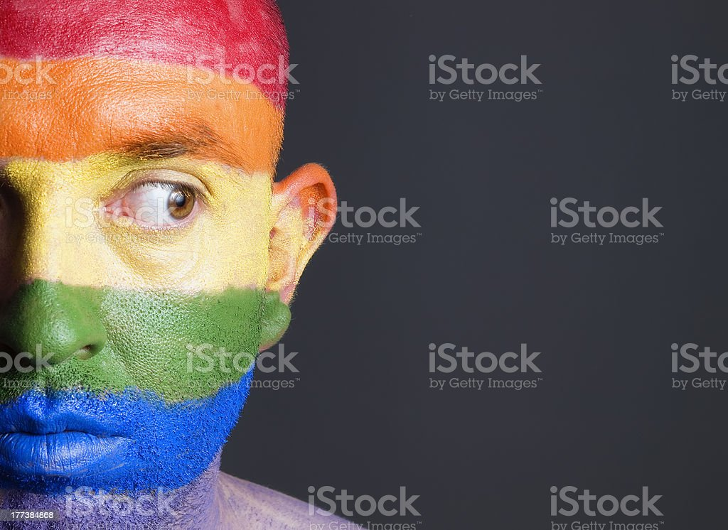 Gay flag painted face man, he is looking sideways stock photo