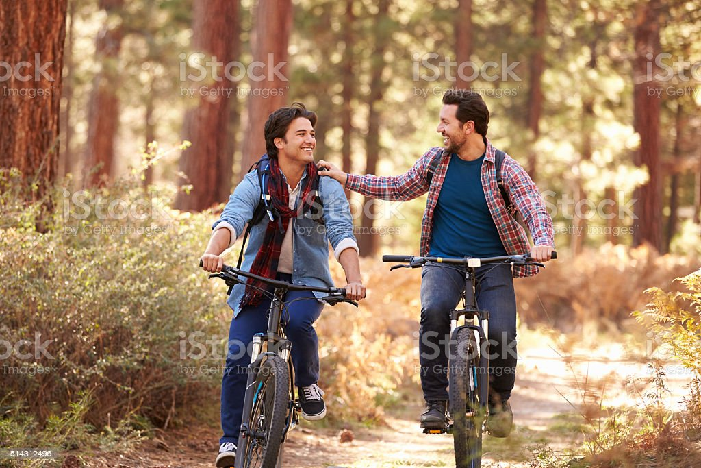 Gay Male Couple Cycling Through Fall Woodland stock photo