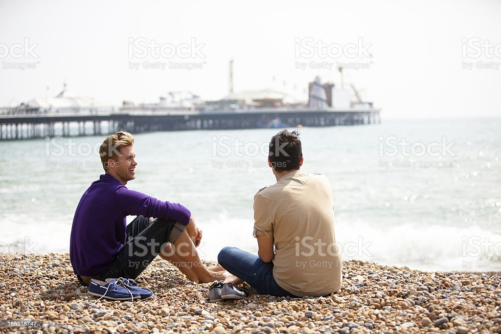 Gay male couple sitting on the beach in Brighton royalty-free stock photo